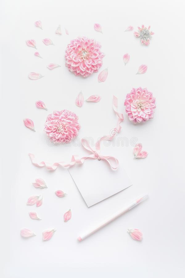 Pastel color mock up with pink flowers and petals, blank paper card with ribbon and point pen on white desktop background, top vie royalty free stock photos