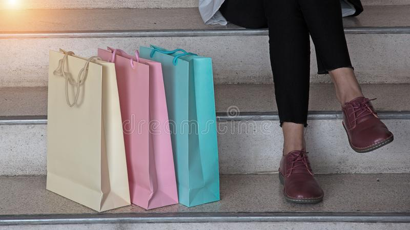 The pastel color of shopping bags put at the left side beside lady is sitting on the stairs stock photos