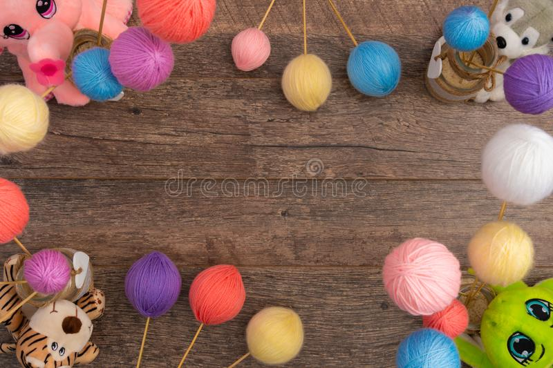 Pastel color yarn balls and stuffed animals. Pastel color wool and plush husky dog, tiger and elephant on wooden background, flat lay, with copy space. Perfect stock photography