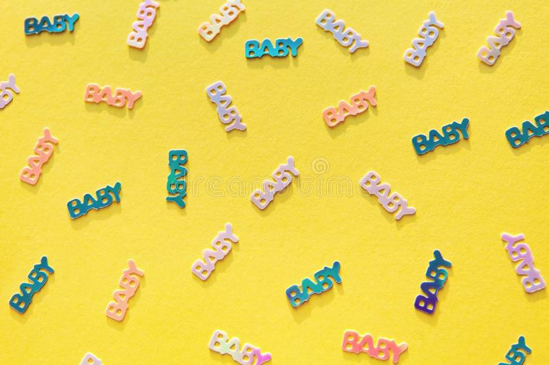 Pastel colored baby confetti on yellow background. Pastel colored confetti with word baby scattered on yellow background. Gender neutral modern trendy baby stock photography