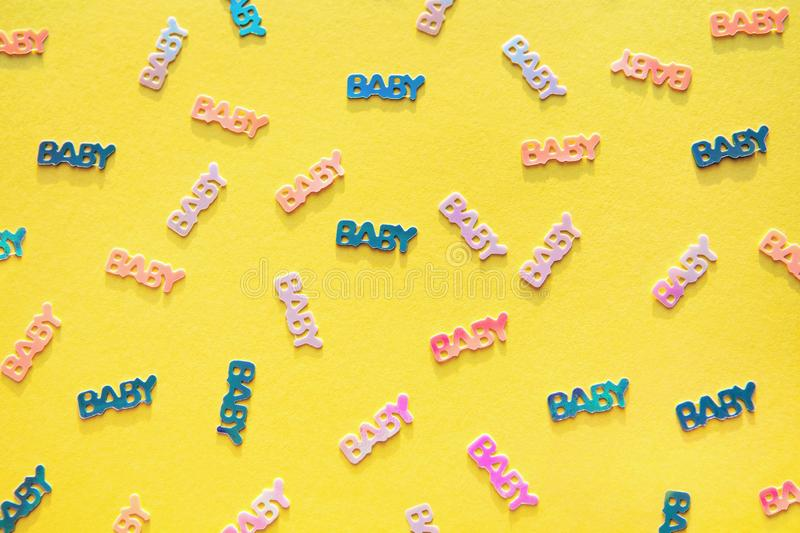 Pastel colored baby confetti on yellow background. Pastel colored confetti with word baby scattered on yellow background. Gender neutral modern trendy baby stock photos