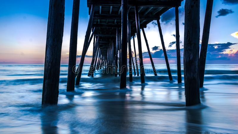 Beautiful long exposure ocean sunrise and gentle waves beneath an old wooden fishing pier. Colors of morning light in the sky. royalty free stock photo