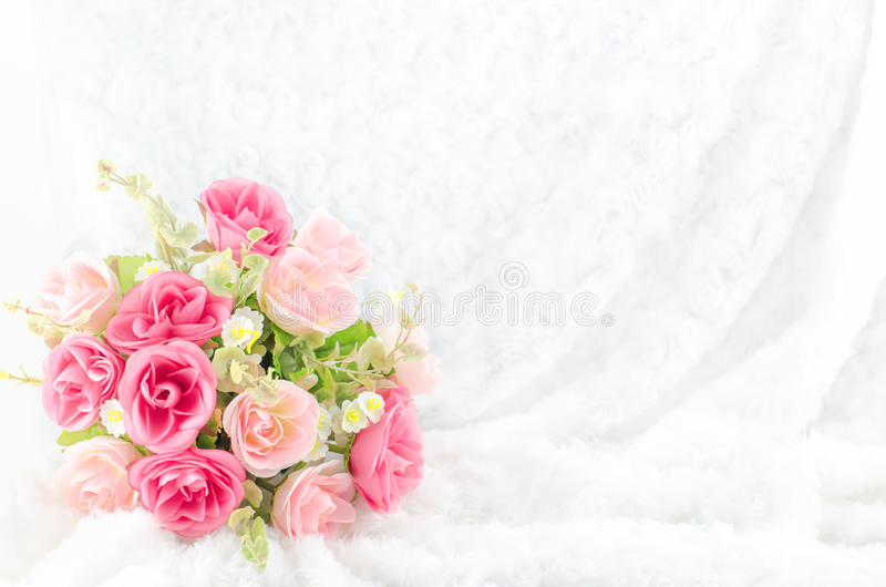 Pastel Coloured Artificial Pink Rose on white fur background. Pastel Coloured Artificial Pink Rose Wedding Bridal Bouquet on white fur background with soft stock photo