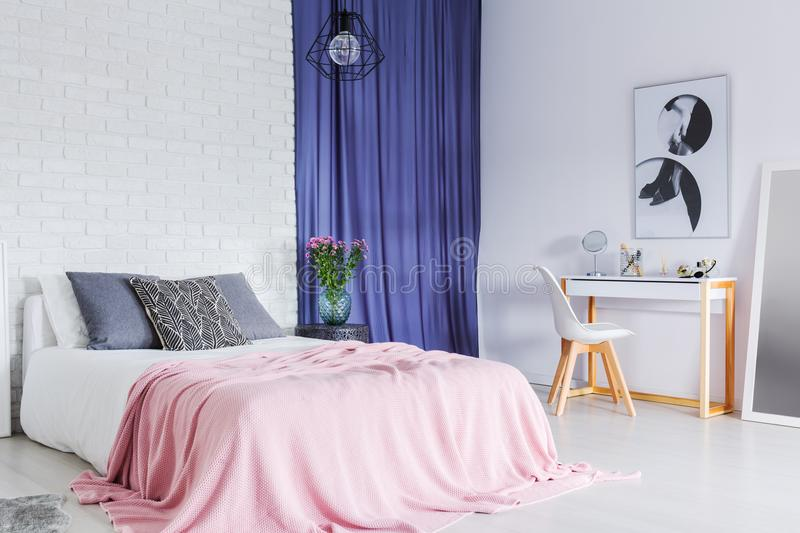 Pastel, contrast bedroom. With white brick wall, pink bed and dark curtains royalty free stock images