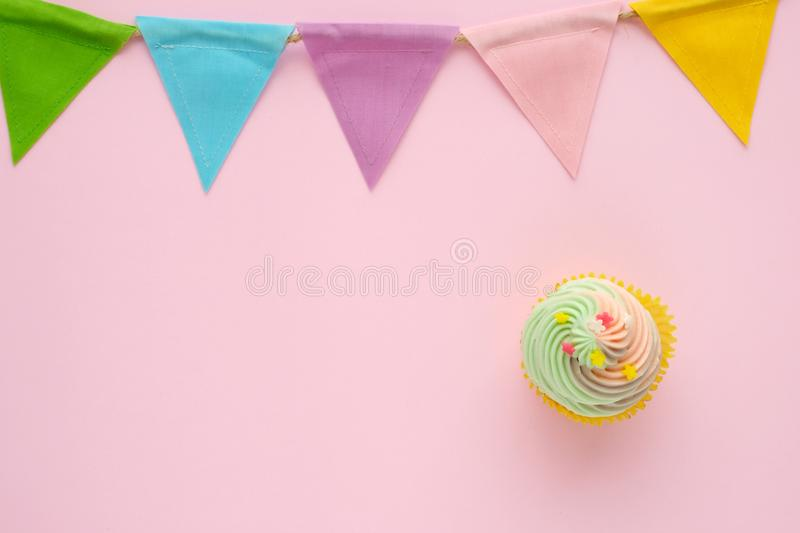 Pastel cupcake and colorful bunting party flag on pink background with copy space for text, birthday, anniversary greeting card b royalty free stock photo