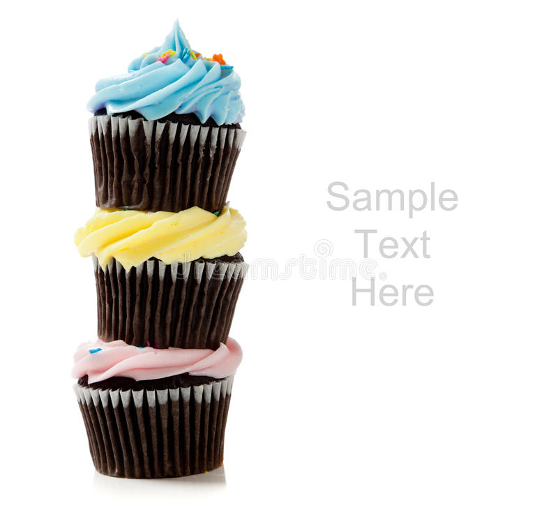 Pastel cupcakes on a white background. Pastel cupcakes including blue, pink and yellow on a white background with copy space stock photo