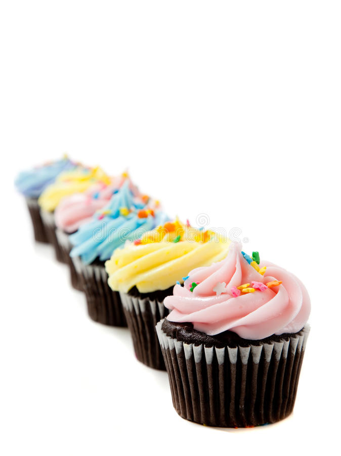 Pastel cupcakes on a white background. Pastel cupcakes including blue, pink and yellow on a white background with copy space royalty free stock images