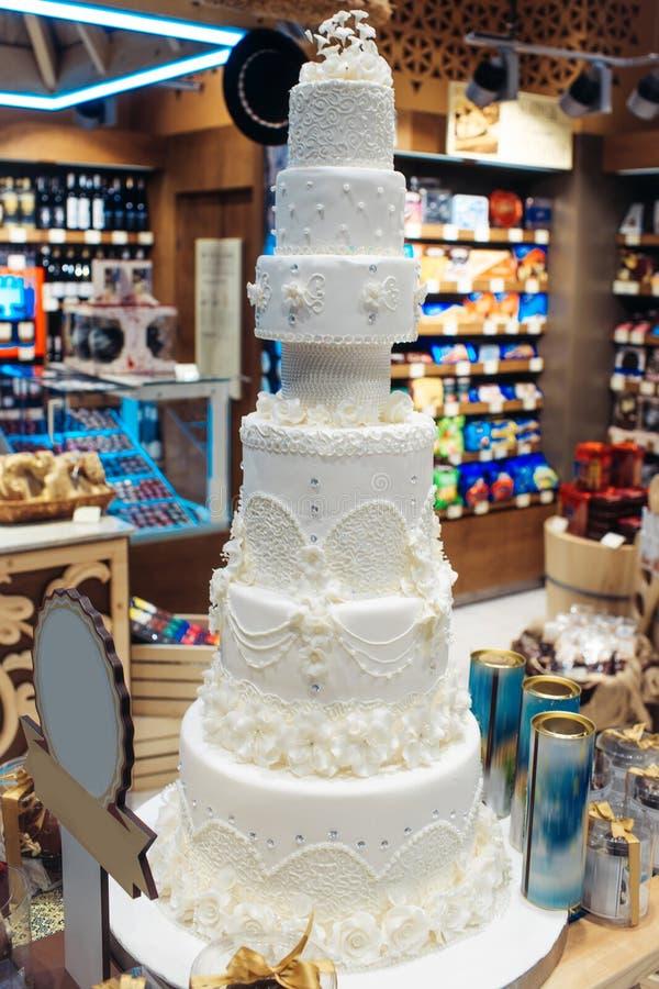Pastel de bodas adornado con las flores en panadería foto de archivo