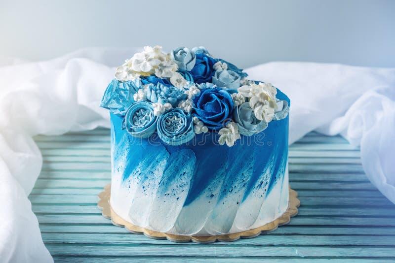 Pastel de bodas azul hermoso adornado con las flores blancas de la crema Concepto de postres del día de fiesta para un cumpleaños fotos de archivo libres de regalías