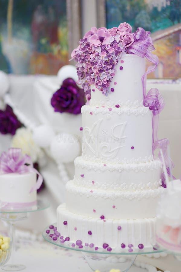Pastel de bodas blanco adornado con las flores púrpuras fotografía de archivo libre de regalías