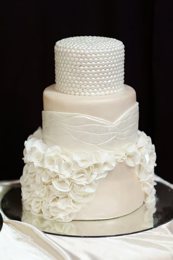 Pastel de bodas blanco adornado con las perlas blancas fotos de archivo libres de regalías