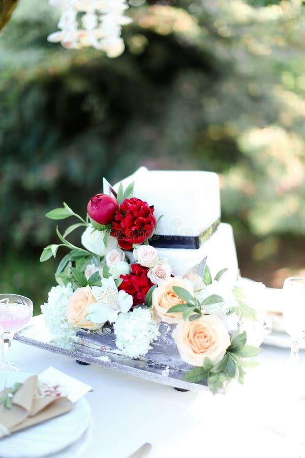 Pastel de bodas blanco con la peonía roja imágenes de archivo libres de regalías