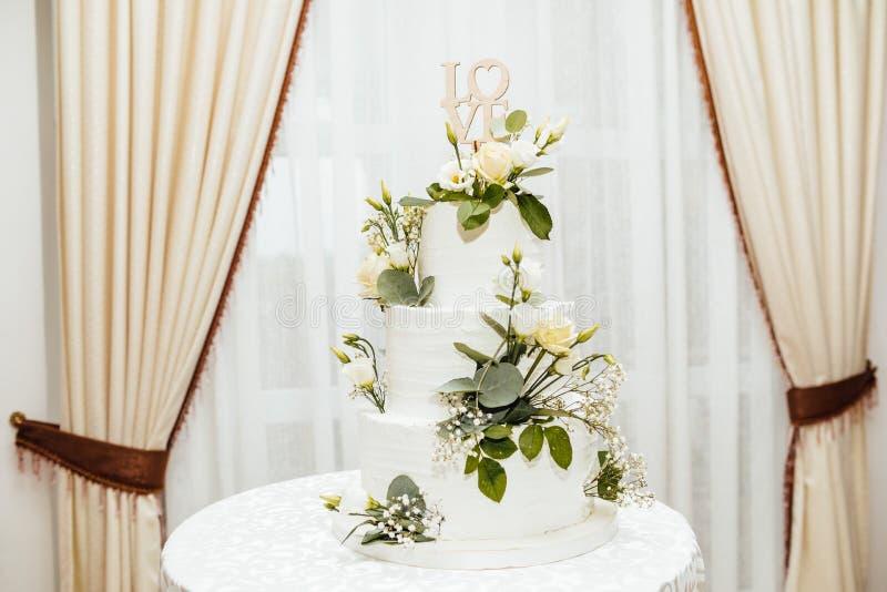 Pastel de bodas blanco con las flores El amor de la palabra con el corazón imagen de archivo libre de regalías