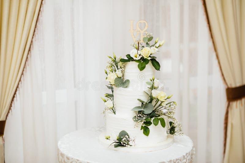 Pastel de bodas blanco con las flores El amor de la palabra con el corazón foto de archivo libre de regalías