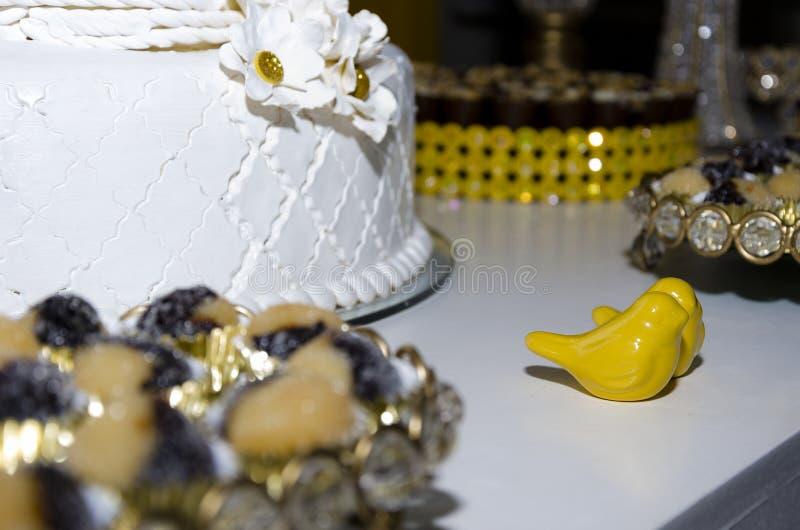 Pastel de bodas blanco con los pájaros de cerámica amarillos foto de archivo