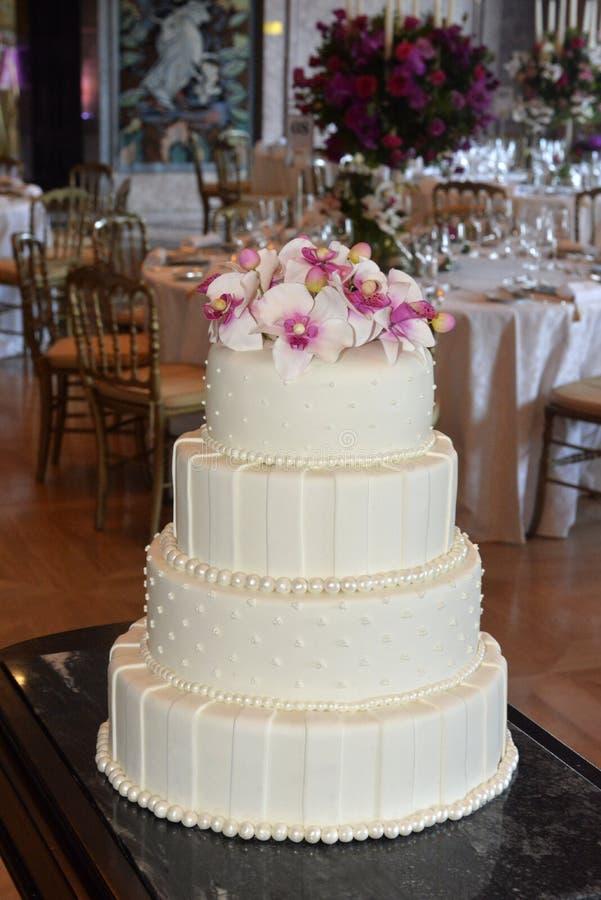 Pastel de bodas blanco de Glacé con las perlas y las flores rosadas, partido de cena fotografía de archivo