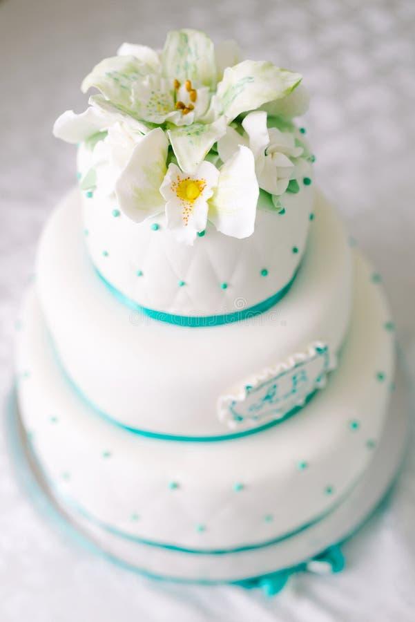 Pastel de bodas blanco de niveles múltiples y flores beige en el top foto de archivo