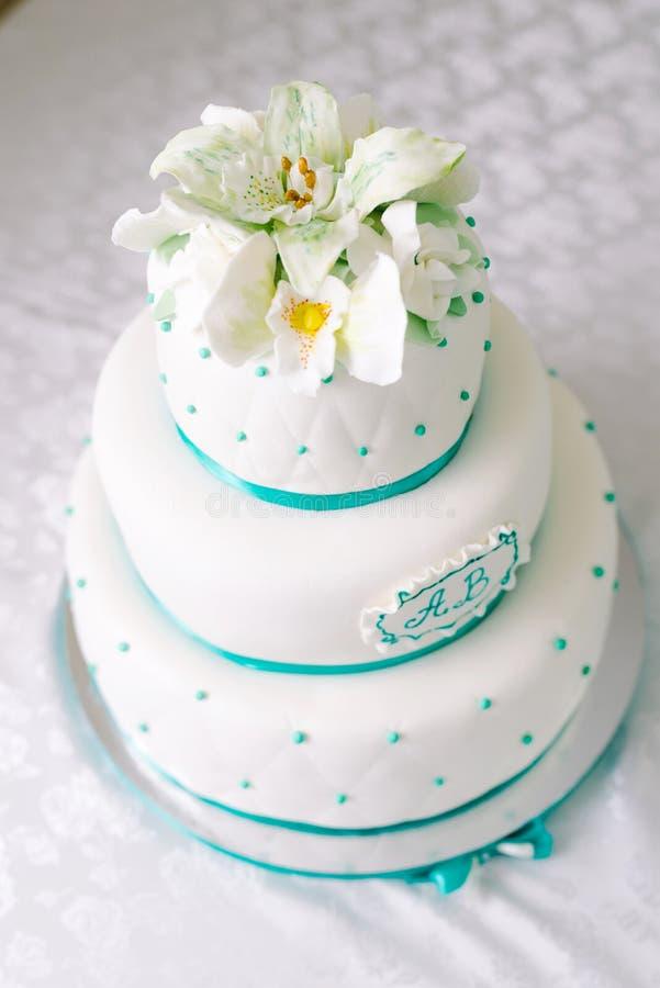 Pastel de bodas blanco de niveles múltiples y flores beige en el top imagen de archivo libre de regalías