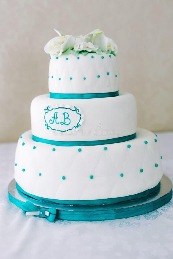 Pastel de bodas blanco de niveles múltiples y flores beige en el top imagenes de archivo