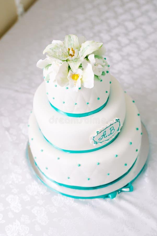 Pastel de bodas blanco de niveles múltiples y flores beige en el top fotos de archivo libres de regalías