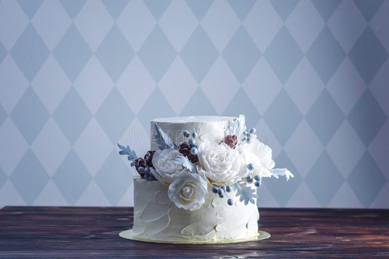Pastel de bodas blanco delicado de la litera adornado con un diseño original usando rosas de la masilla Concepto de postres festi foto de archivo libre de regalías
