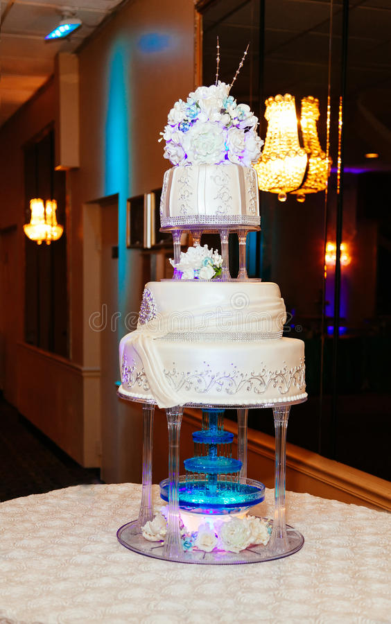 pastel de bodas blanco llano multi en una base de plata y flores rosadas en el top fotos de archivo