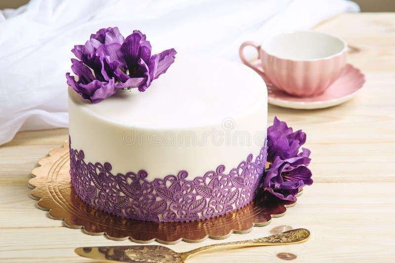 Pastel de bodas casero hermoso adornado con las peonías púrpuras en un estilo rústico en fondo de madera fotografía de archivo