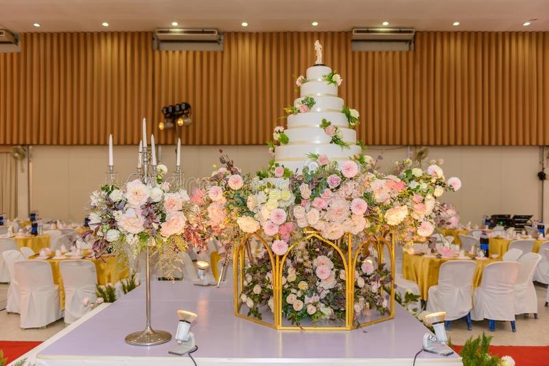Pastel de bodas con adornado con las flores y la palmatoria en la ceremonia de matrimonio imágenes de archivo libres de regalías
