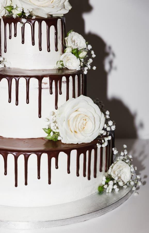 Pastel de bodas con el chocolate y las flores fotos de archivo libres de regalías