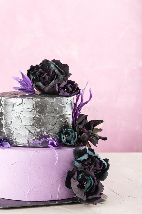 Pastel de bodas con gradas con las flores falsas negras en fondo rosado foto de archivo