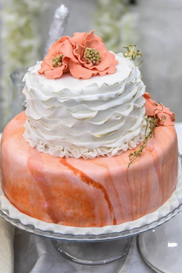 Pastel de bodas con las decoraciones blancas y anaranjadas fotografía de archivo