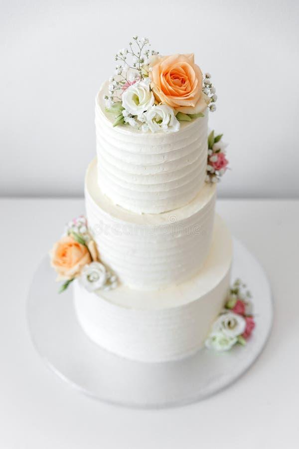 Pastel de bodas con las flores en un fondo blanco fotos de archivo
