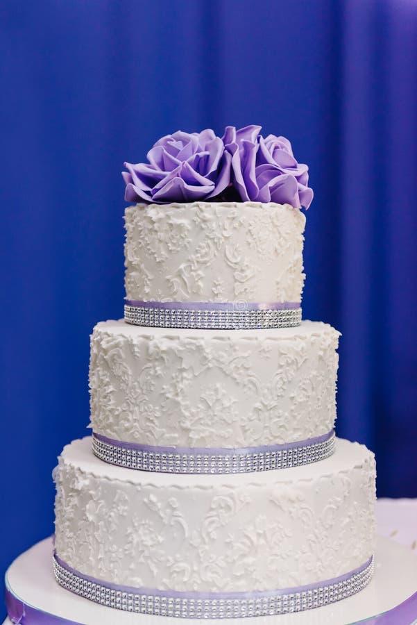 Pastel de bodas con las flores púrpuras, pastel de bodas foto de archivo libre de regalías