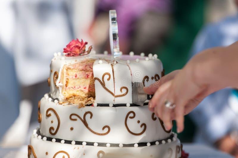 Pastel de bodas con las manos, el cuchillo y las rebanadas del corte foto de archivo