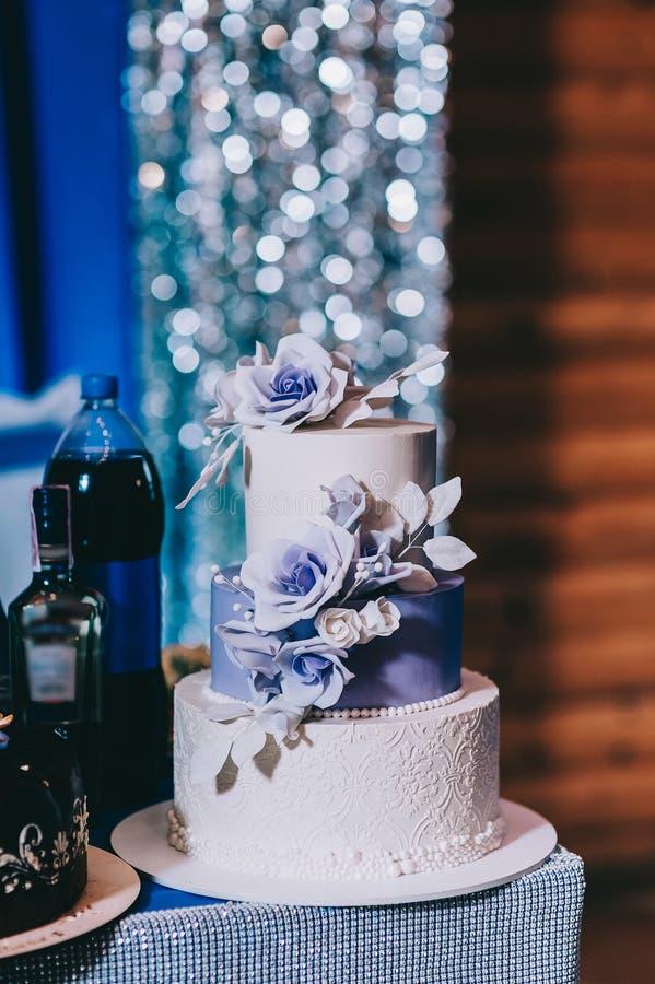 Pastel de bodas con los azules turquesa rojos beige amarillos de las flores imagen de archivo libre de regalías