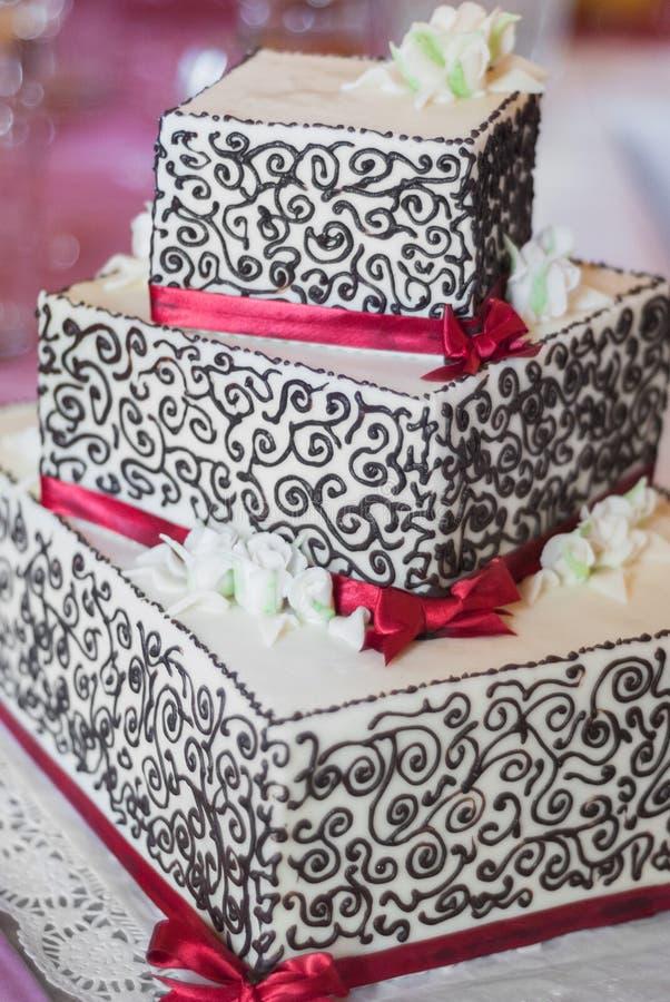 Pastel de bodas cuadrado de tres niveles foto de archivo libre de regalías