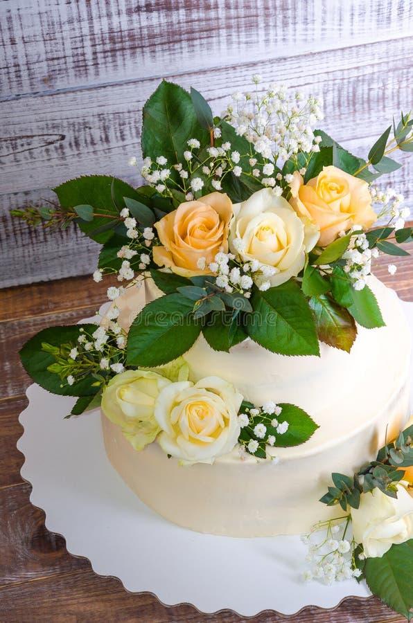 Pastel de bodas de dos pisos con el eucalipto de las rosas foto de archivo