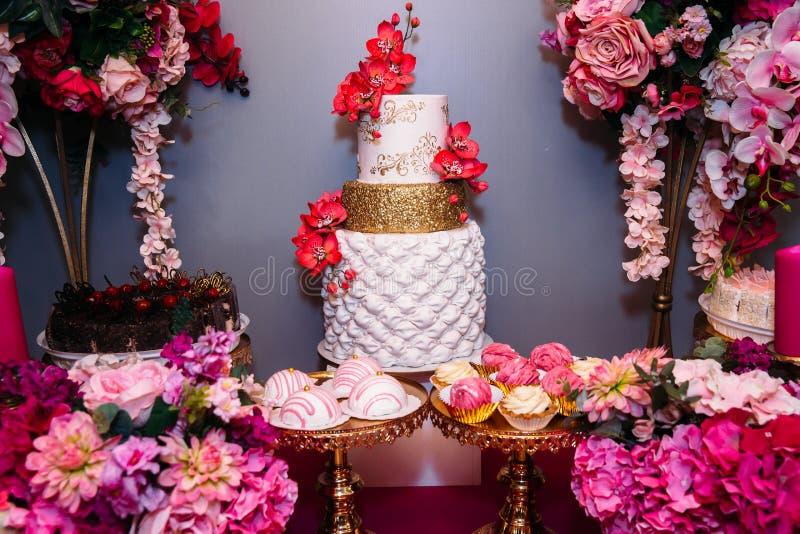 Pastel de bodas de niveles múltiples dulce adornado con las flores hermosas Barra de caramelo imagen de archivo libre de regalías