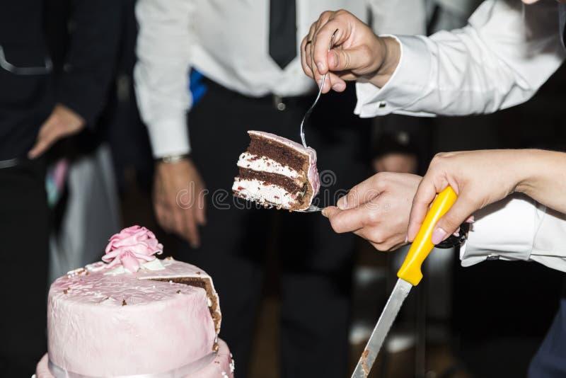 Pastel de bodas del corte de novia y del novio cerca de huéspedes foto de archivo