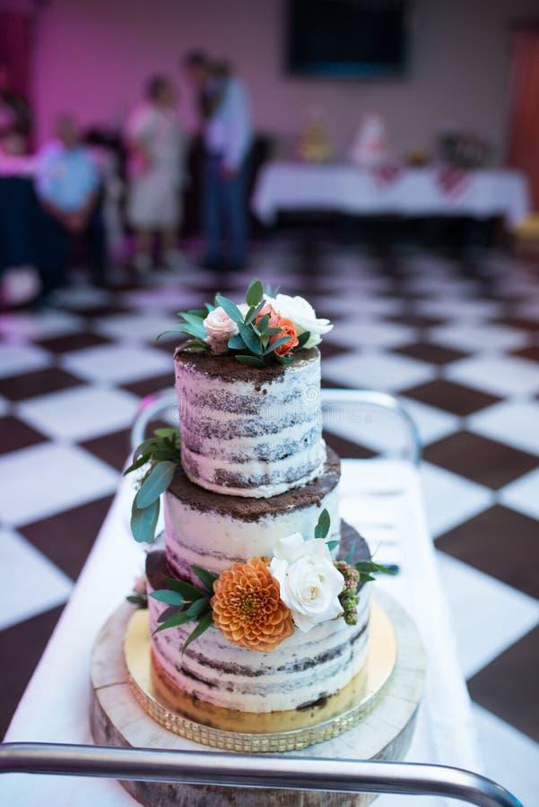 Pastel de bodas en estilo rústico Torta con gradas de la galleta de la boda del chocolate tres adornada con las flores blancas y  fotografía de archivo