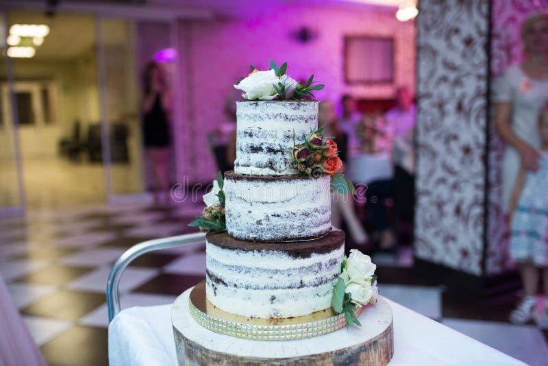 Pastel de bodas en estilo rústico Torta con gradas de la galleta de la boda del chocolate tres adornada con las flores blancas y  fotografía de archivo libre de regalías