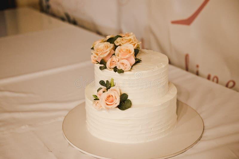 Pastel de bodas festivo con las flores, flores rosado-anaranjadas, litera, hermosa fotos de archivo