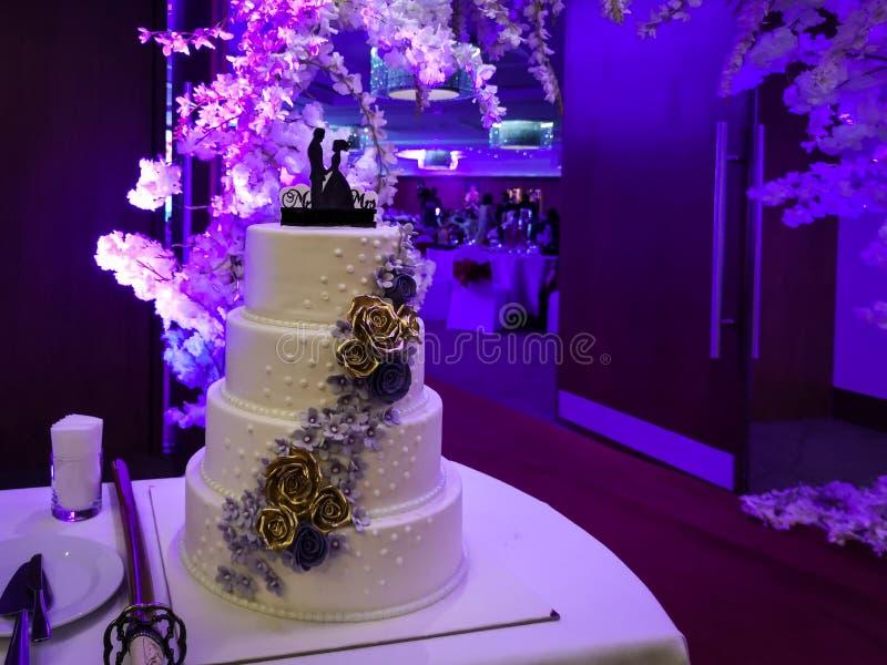 Pastel de bodas fuera de un pasillo que escarda en la noche con las luces púrpuras imagenes de archivo