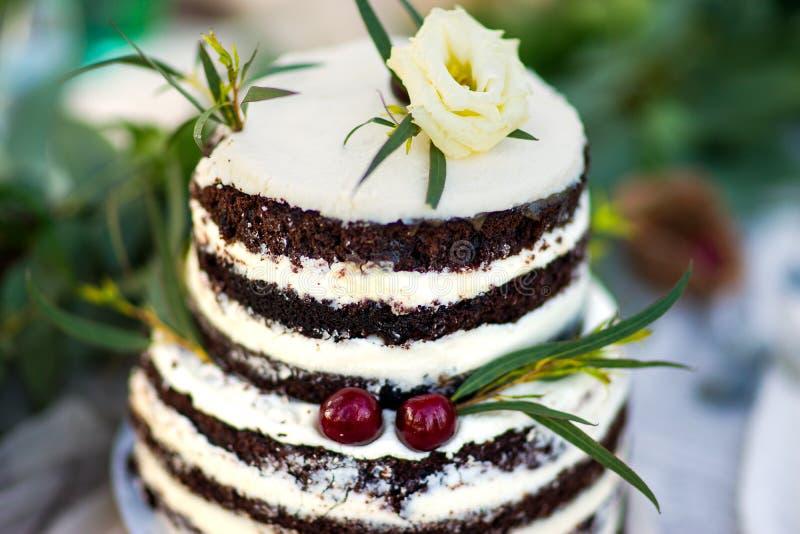 Pastel de bodas hermoso adornado con las flores y verdor y cereza amarillos dos Torta para el cumpleaños u otros días de fiesta foto de archivo