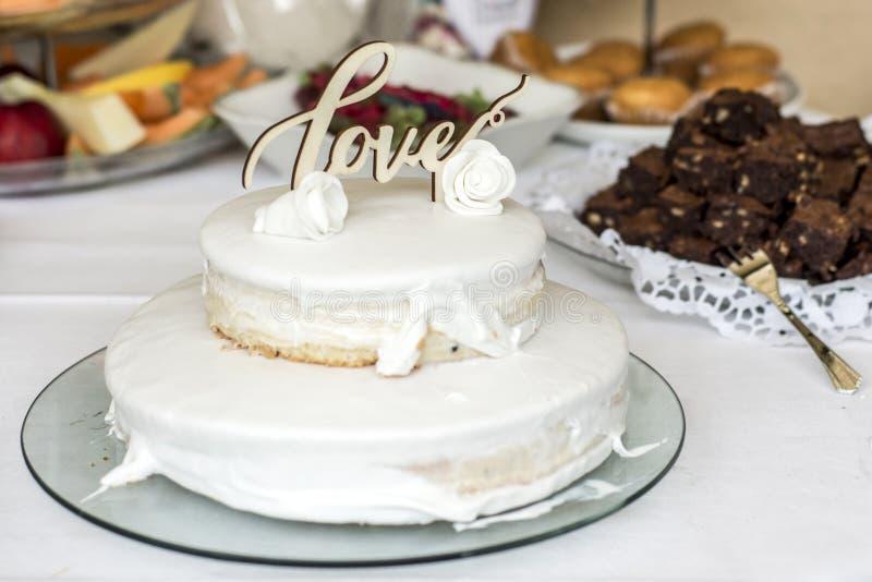 Pastel de bodas hermoso con crema con amor del texto en rosas superiores de las flores blancas imagenes de archivo