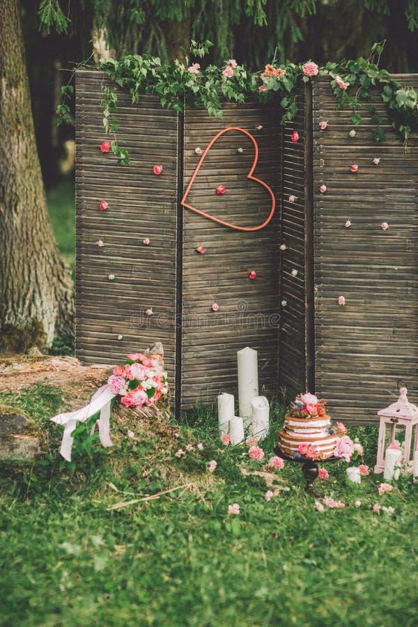 Pastel de bodas hermoso con las flores, las velas y las decoraciones al aire libre imágenes de archivo libres de regalías