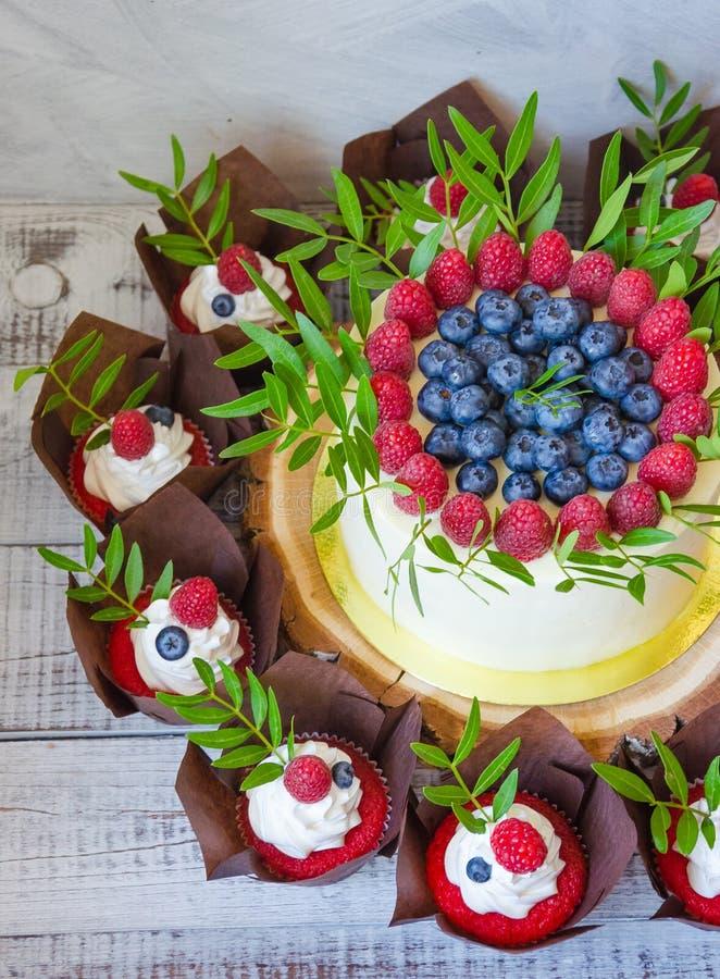 Pastel de bodas de la baya y magdalenas rojas del terciopelo foto de archivo libre de regalías