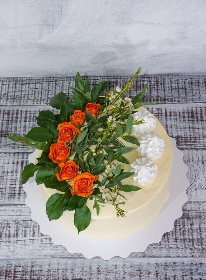 Pastel de bodas de la vainilla del queso cremoso con las rosas anaranjadas imagen de archivo libre de regalías