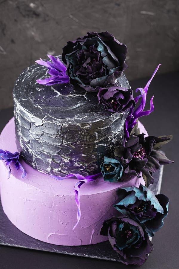 Pastel de bodas de las ilustraciones con las flores falsas en fondo negro fotografía de archivo
