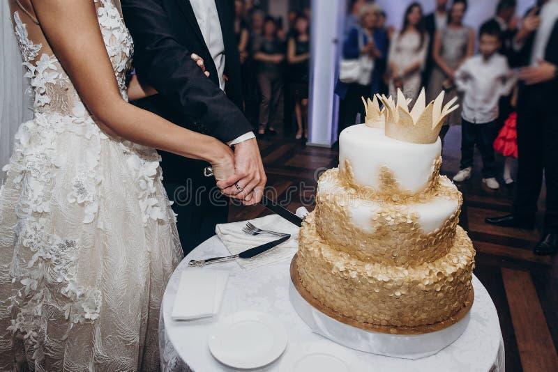 Pastel de bodas de oro novia y novio que cortan junto su oro fotografía de archivo
